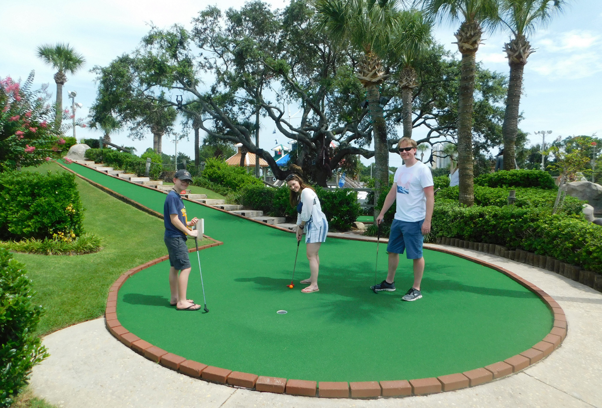 An image of a family having fun playing mini-golf at Coconut Creek in Panama City Beach, Florida.